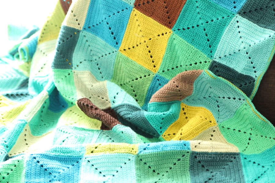 Häkeldecke aus einfarbigen Granny Squares in türkis, grün und braun